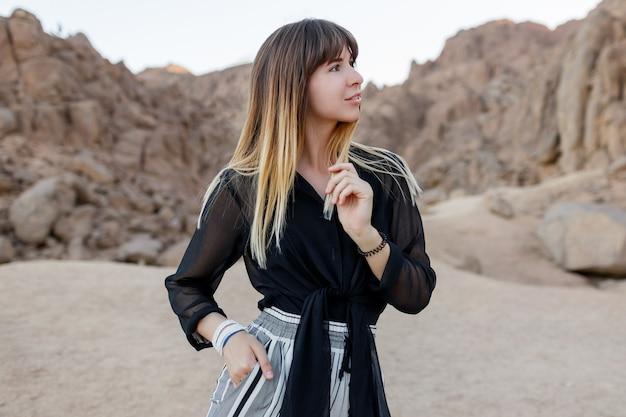 Elegante brunette vrouw poseren in de egyptische woestijnzandduinen.