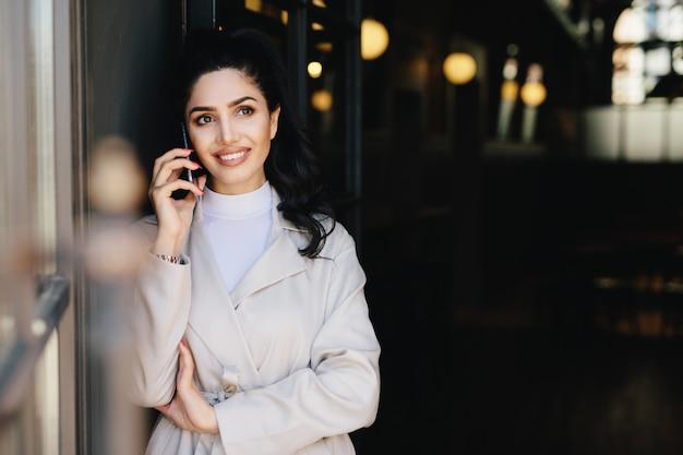 Elegante brunette zakenvrouw met donkere ogen en volle lippen gekleed in witte kleren