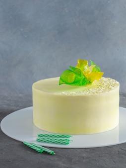 Elegante cake met gele, groene bloemendecoratie en verjaardagskaarsen op grijs
