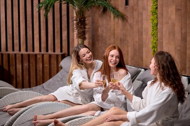 Elegante charmante vrouwen die glas op champagne in de hand houden en genieten van een geweldige tijd in het kuuroordhotel