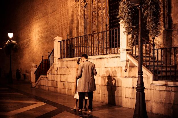 Elegante dame dichtbij jonge kerel op straat in avond