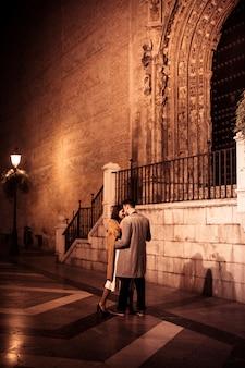 Elegante dame die met jonge kerel op straat in avond koestert