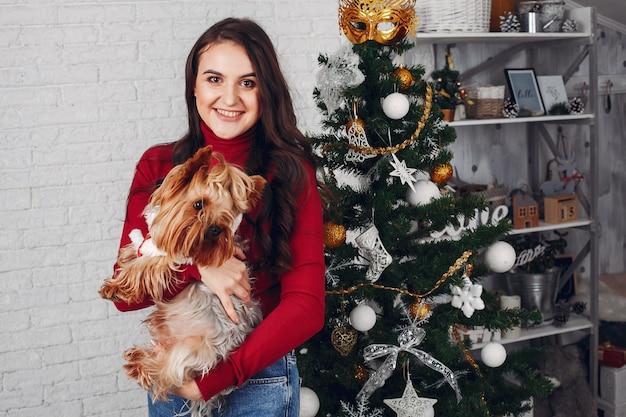 Elegante dame die zich dichtbij kerstboom bevindt