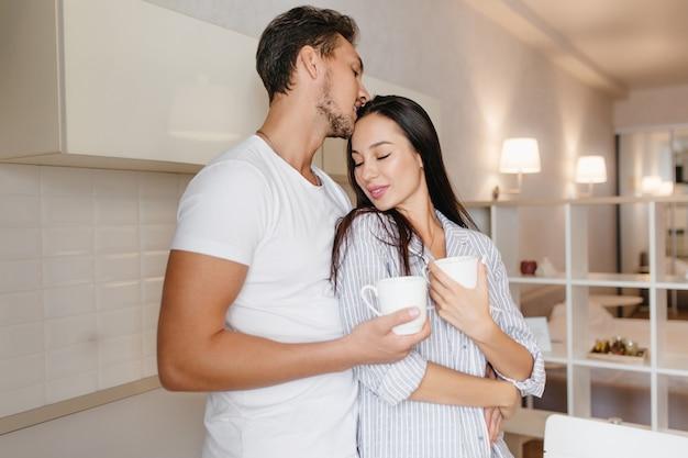 Elegante dame draagt gestreepte pyjama knuffelt haar vriendje met een kopje koffie