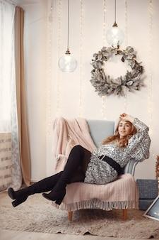Elegante dame in de buurt van de kerstboom. vrouw in een kamer. famale in een zilveren jurk.