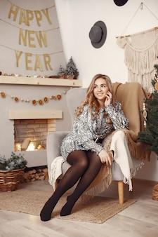 Elegante dame in de buurt van de kerstboom. vrouw in een kamer.