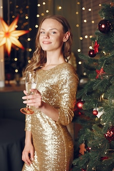 Elegante dame in de buurt van de kerstboom. vrouw thuis met champagne.
