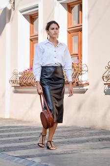 Elegante dame in lederen rok en wit shirt op straat met lederen handtas