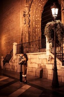 Elegante dame knuffelen en hand in hand met jonge kerel op straat