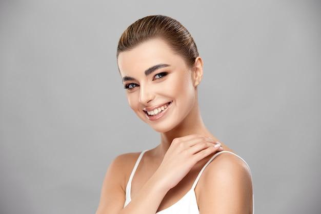 Elegante dame met perfecte huid en lichte make-up glimlachend en haar schouder aanraken, schoonheidsconcept, exemplaarruimte