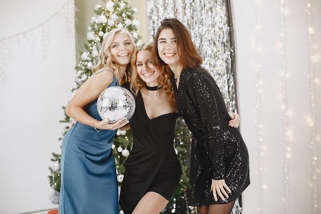 Elegante dames dichtbij kerstboom. vrouwen in elegante kleding.