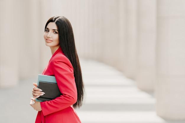 Elegante donkerbruine dame met donker lang steil haar, gekleed in modieus rood pak