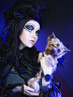 Elegante donkere koningin met kleine hond