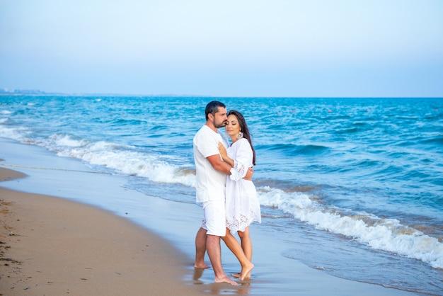 Elegante en aantrekkelijke gelukkige familie man en vrouw wandelen aan de zeekust. jonge vrouw en man verliefd.