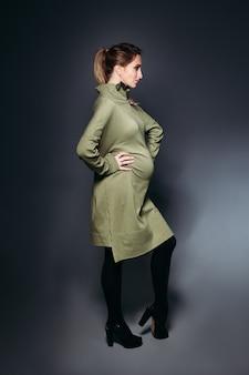 Elegante en modieuze zwangere donkerbruine vrouw.