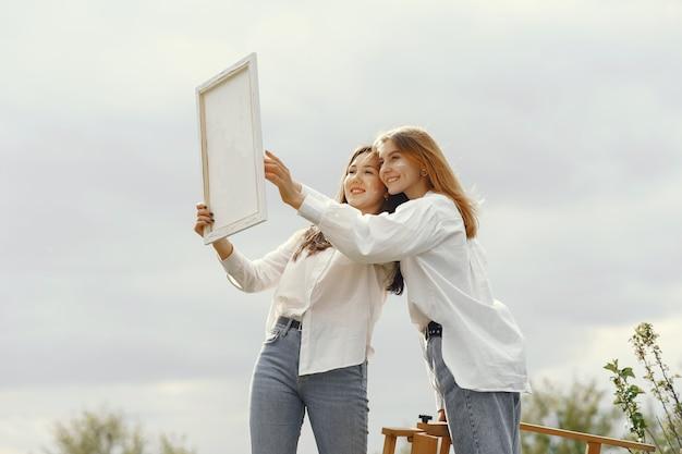 Elegante en mooie meisjes schilderen in een veld