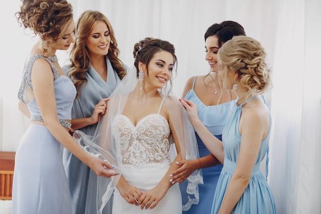 Elegante en stijlvolle bruid samen met haar vier vrienden in blauwe jurken staan in een kamer