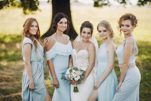 Elegante en stijlvolle bruid samen met haar vier vrienden in blauwe jurken staan in een park