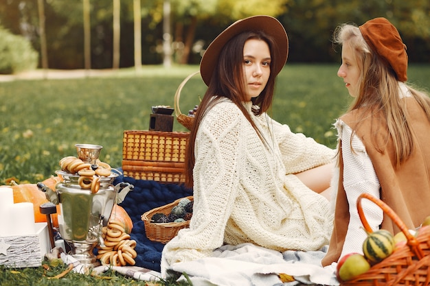 Elegante en stijlvolle meisjes zitten in een herfst park
