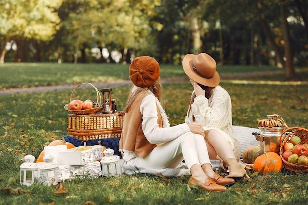 Elegante en stijlvolle meisjes zitten in een park