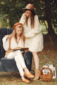 Elegante en stijlvolle meisjes zitten op een stoel in een park het lezen van een boek