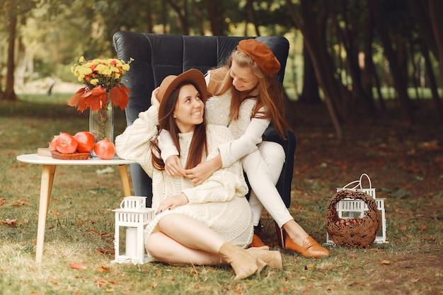 Elegante en stijlvolle meisjes zitten op een stoel in een park