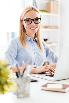 Elegante en vrolijke zakenvrouw. vrolijke jonge mooie vrouw met een bril die met een glimlach naar de camera kijkt terwijl ze op haar werkplek zit