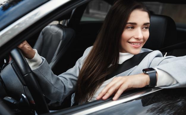 Elegante en zelfverzekerde onderneemster die uit autoraam kijkt, op het werk rijdt, veiligheidsgordel draagt voor veiligheid