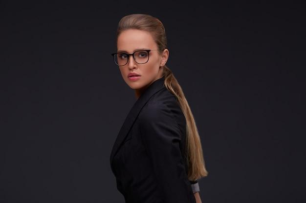 Elegante ernstige vrouw in vierkante brillen. volwassen mooie zakenvrouw in pak