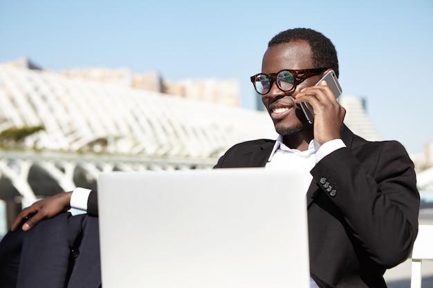 Elegante financier met gesprek over smartphone zittend op openluchtrestaurant