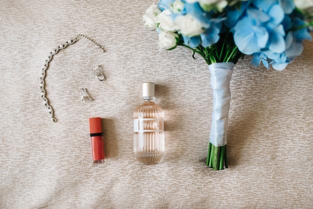 Elegante fles parfum op de fauteuil met een roze ketting van de bruid