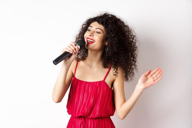 Elegante gekrulde vrouw in rode jurk zingen in de microfoon, opzij kijken en glimlachend gelukkig, staande op een witte achtergrond.