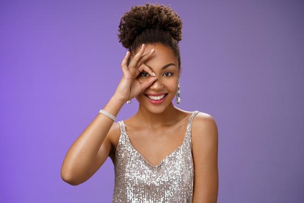 Elegante gelukkige zelfverzekerde vrouwelijke afro-amerikaanse vrouw in zilveren modieuze jurk toont oke ok gebaar op oog glurend naar voren graag glimlachend zelfverzekerd als perfectie, staan blauwe achtergrond.
