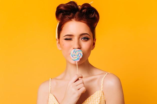 Elegante gember meisje likt lolly. vooraanzicht van enthousiaste vrouw met hard snoep.