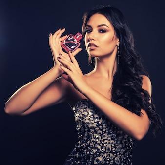 Elegante glamourvrouw in een mooie jurk met parfum op donkere ruimte.