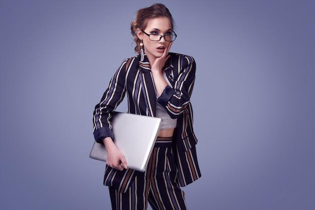 Elegante glamourvrouw in manierkostuum en glazen met notitieboekje