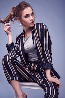 Elegante glamourvrouw in manierkostuum het stellen op kleurrijk blauw