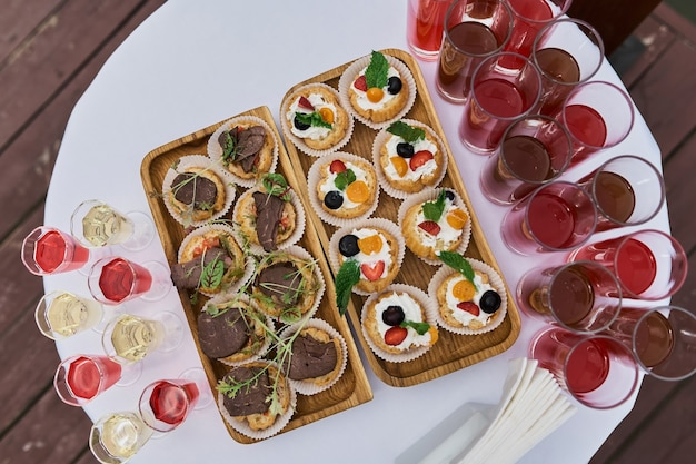 Elegante glazen met gekoelde champagne staan in de rij naast hapjes en snacks op een schilderachtige achtergrond. feest en vakantie weg. picknick.