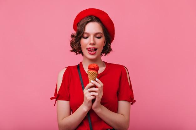 Elegante goedgeklede vrouw die van dessert geniet. krullend frans meisje dat roomijs eet.