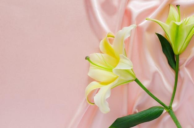 Elegante golvende en gladde roze satijnen doek textuur achtergrond met lelie bloemen