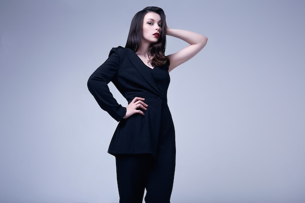 Elegante gotische donkerbruine vrouw met rode lippen in zwart kostuum
