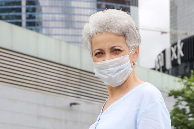 Elegante grijsharige vrouw op straat in een medisch masker