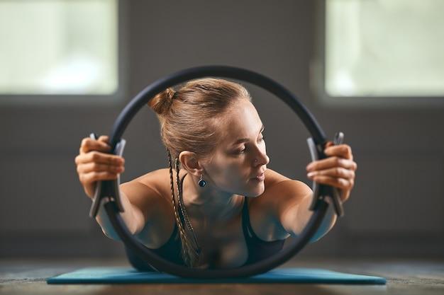 Elegante gymnastiekleraar omgekeerde handen ondersteunen lichaam op vloer en benen op pilatesring met stretchlichaam ontwikkelen zachtheid in grijze muur oppervlakte studio