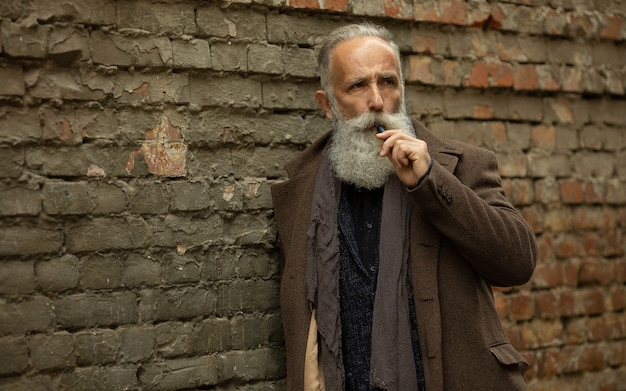 Elegante heer met lange baard buiten roken.