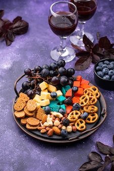 Elegante herfsthapjes. kaasplaat met bessen, druiven, noten en snacks