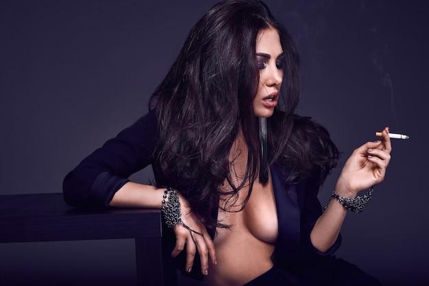 Elegante hete donkerbruine vrouw die een sigaret op zwarte muur rookt