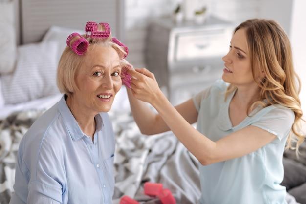 Elegante hogere vrouw die roze haarrollen draagt en hulp ontvangt met extra stukken van haar mooie jonge dochter