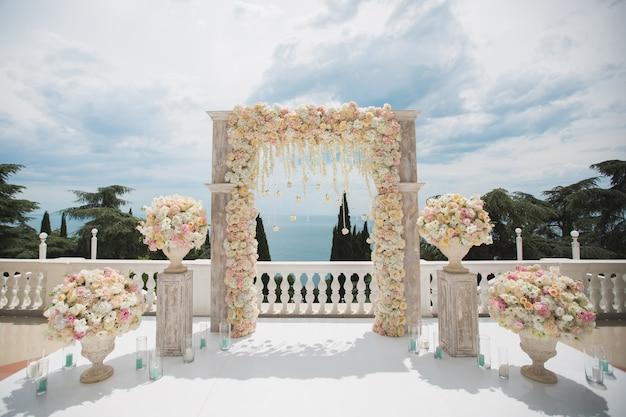 Elegante huwelijksboog met verse bloemen, vazen op achtergrond van oceaan en blauwe hemel.