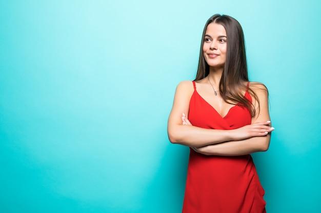 Elegante jonge aantrekkelijke vrouw, gekleed in rode zomerjurk met gekruiste handen geïsoleerd over pastel blauwe muur.
