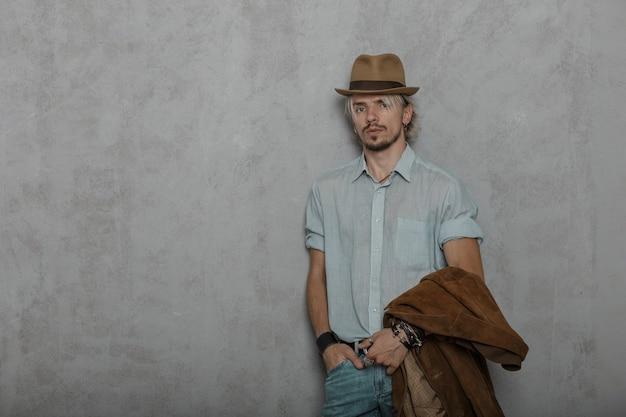 Elegante jonge bebaarde hipster man in een vintage bruine hoed met een bruin modieus jasje in een klassiek shirt poseren in een kamer in de buurt van een grijze muur.